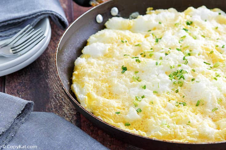 a fluffy omelette in a pan next to forks, plates, and blue napkins