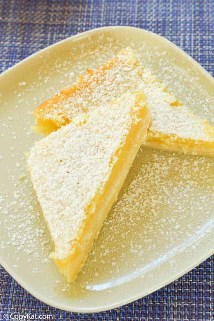 two lemon bars dusted with powdered sugar