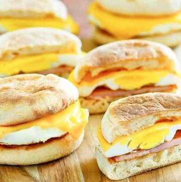 four homemade egg mcmuffins on a wood platter