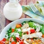 a bottle of creamy pesto dressing next to a salad with grilled chicken