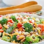 broccoli salad with salad tongs and bowls behind it.