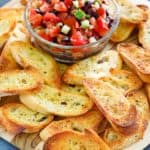 crostini and bowl of tomato topping on a platter