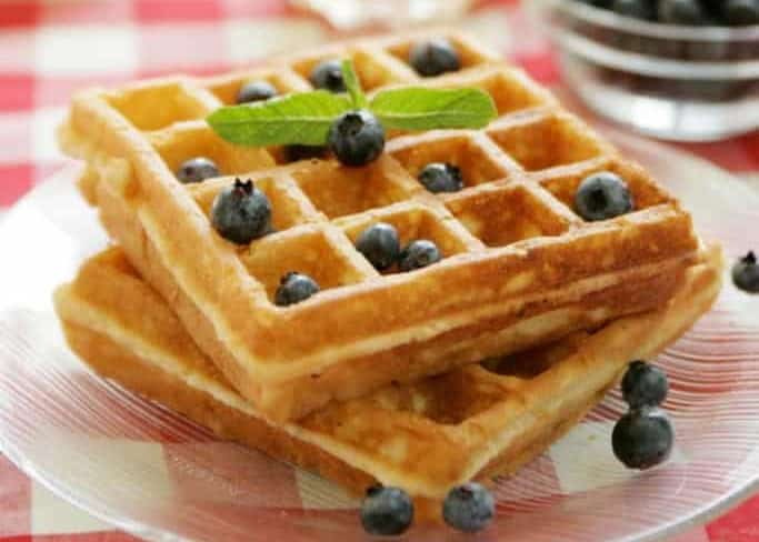 two waffles and blueberries on a plate