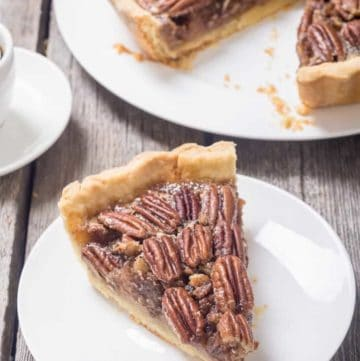 a slice of pecan pie on a white plate next to the pie