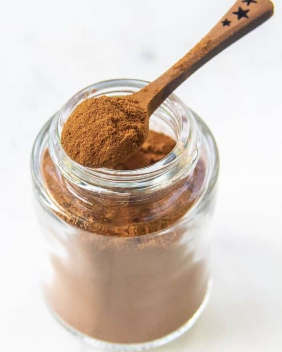 homemade pumpkin pie spice mix in a small spoon on top of a spice jar