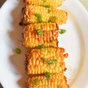 air fried corn on the cob on a white platter