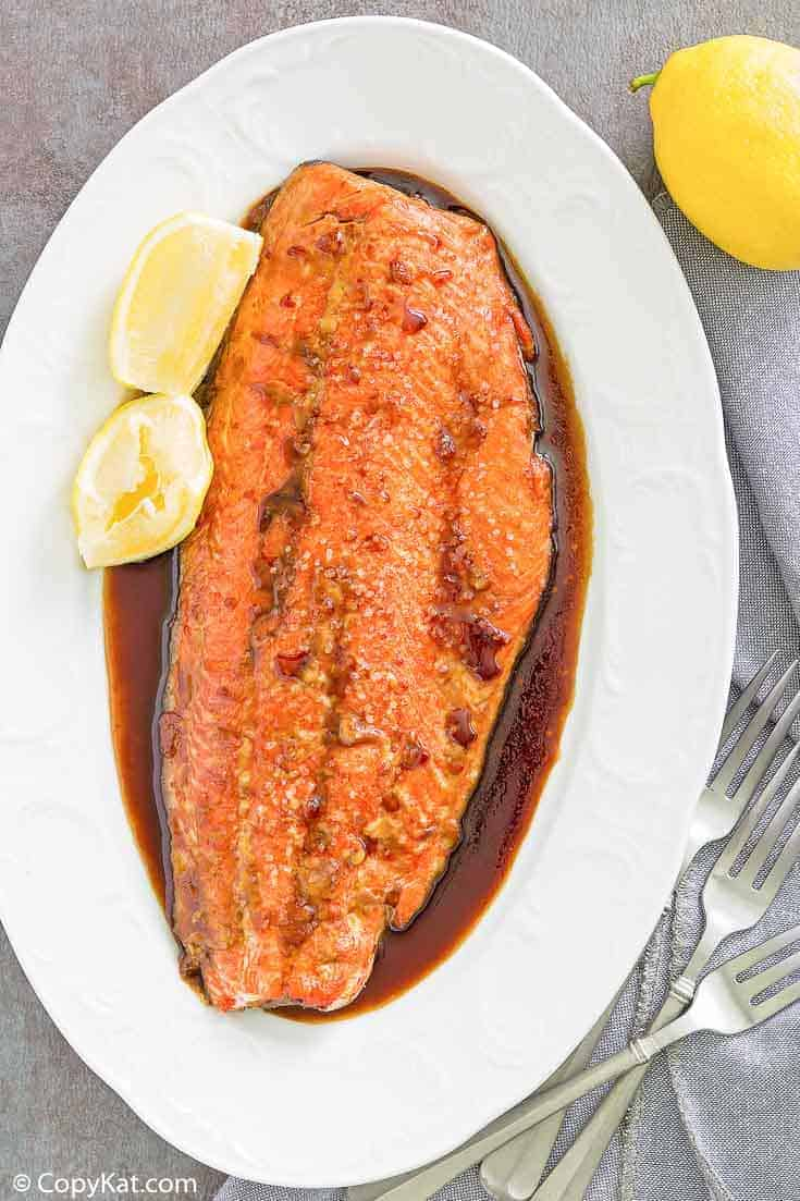 baked salmon with sauce and lemon wedges on a platter