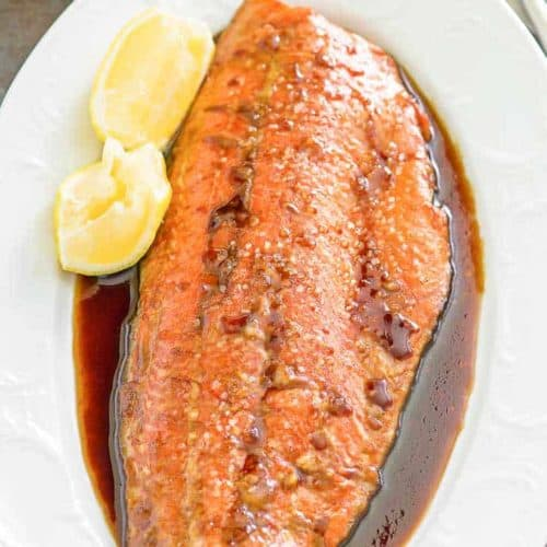 baked salmon, sauce, and lemon wedges on a platter