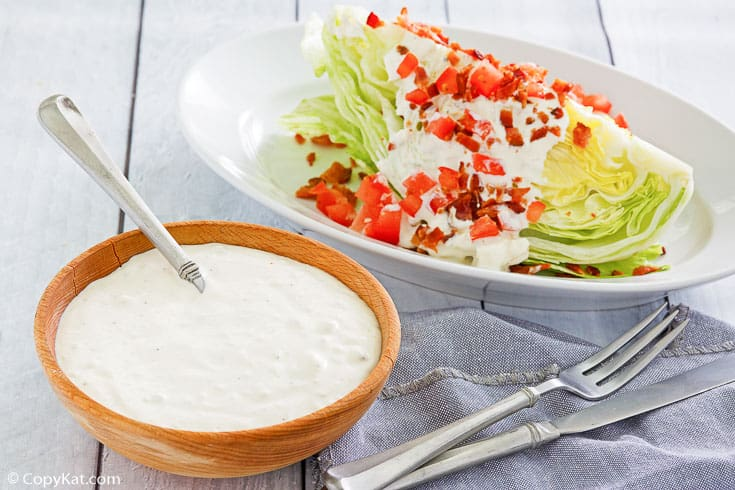 a bowl of homemade blue cheese dressing beside a wedge salad