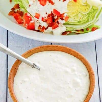 a bowl of blue cheese dressing next to a wedge salad
