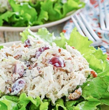 chicken salad with grapes, apples, and pecans on top of lettuce on a plate