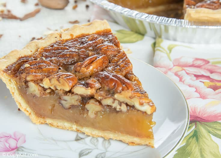 a slice of homemade pecan pie on a white plate with pink flowers