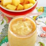 a bowl of pineapple pieces and a dole whip with rum float in a glass