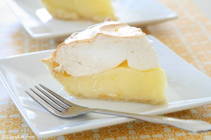 a slice of lemon meringue pie and a fork on a square white plate