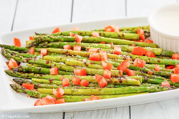 parmesan roasted asparagus, balsamic drizzle, chopped tomatoes, and cheese sauce on a platter