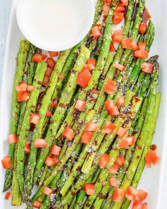 Homemade Olive Garden Parmesan Roasted Asparagus with balsamic drizzle and cheese sauce on a platter