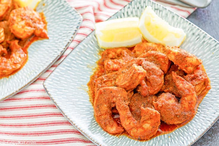 Cajun shrimp and lemon wedges on a blue plate