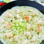a bowl of cream of celery soup topped with croutons