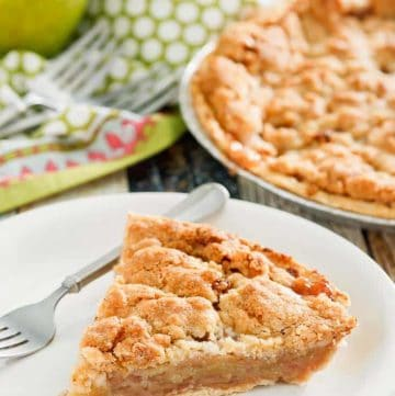 a slice of Dutch apple pie and a fork on a plate with the pie and apples in the background