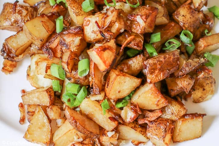 oven roasted potatoes topped with chopped green onions on a platter