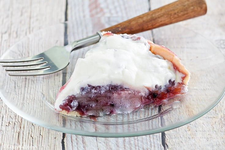 a slice of sour cream blueberry pie and a fork on a plate