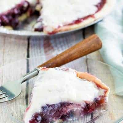 sour cream blueberry pie slice and a fork on a plate