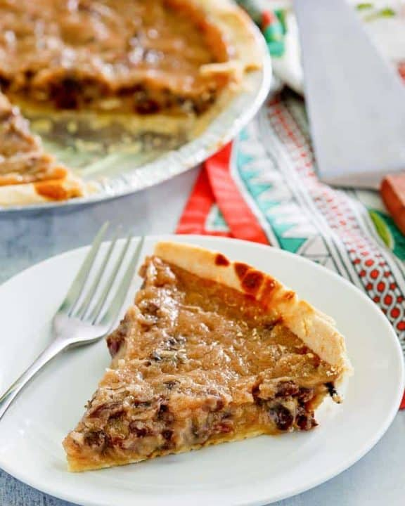 a slice of sour cream raisin pie on a plate next to the pie