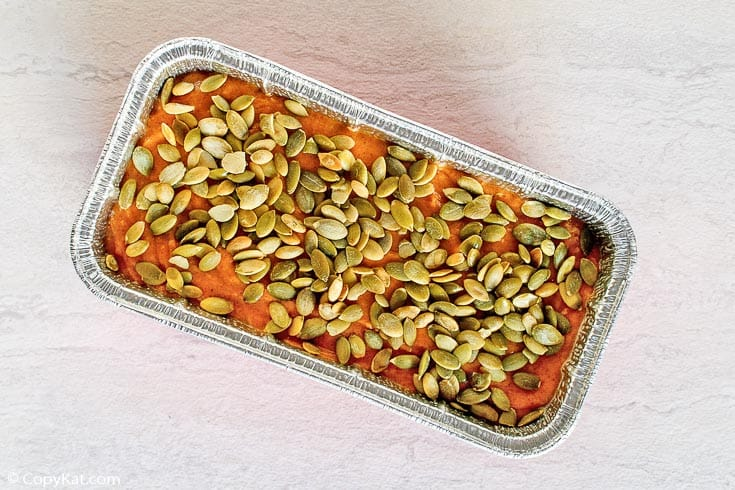pumpkin bread batter topped with pumpkin seeds in a loaf pan before baking