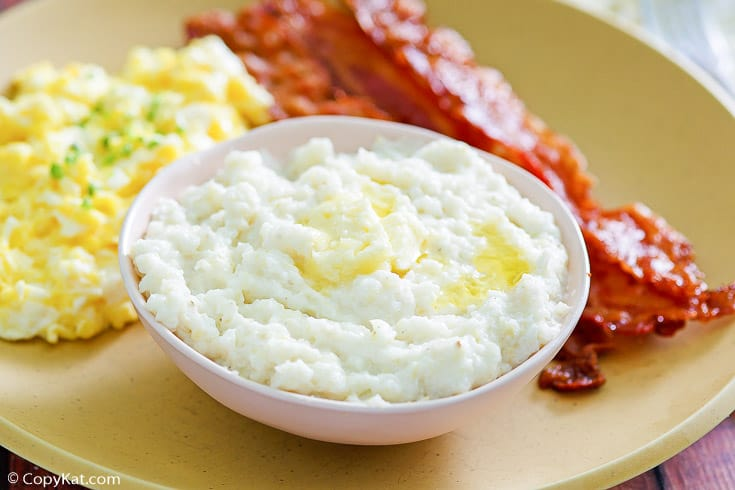 a bowl of homemade Luby's grits on a plate with eggs and bacon