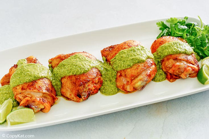 Peruvian chicken thighs topped with green sauce on a platter