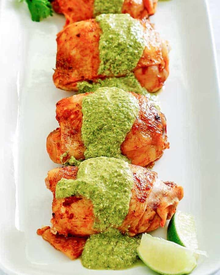 four Peruvian chicken thighs with green sauce on a platter