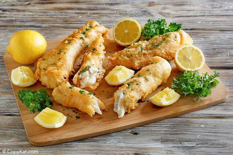 batter fried fish and lemon wedges on a wood platter