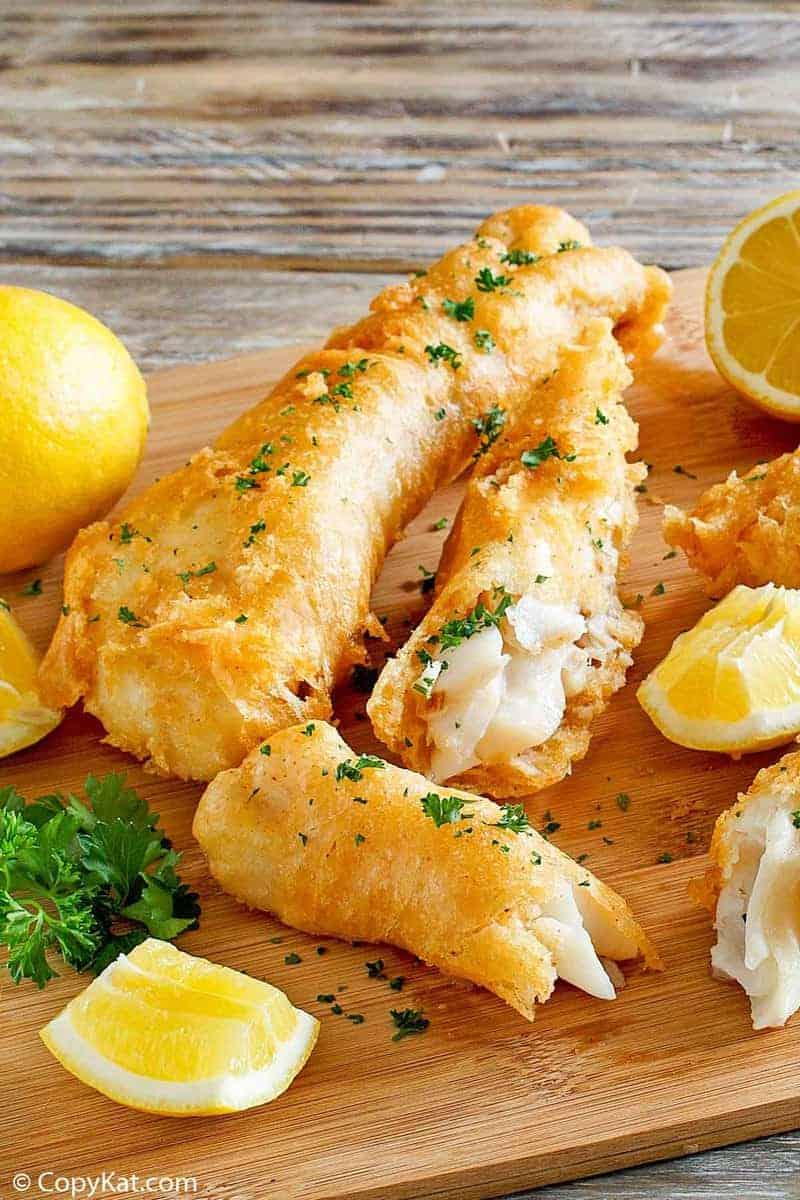 Homemade Captain D's batter dipped fish and lemons on a wood platter