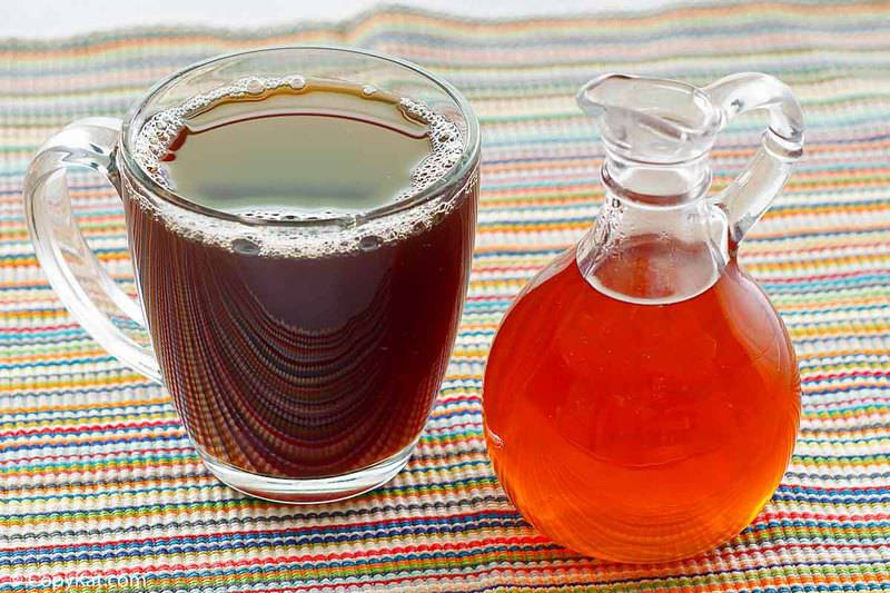 a container of caramel syrup and a cup of coffee