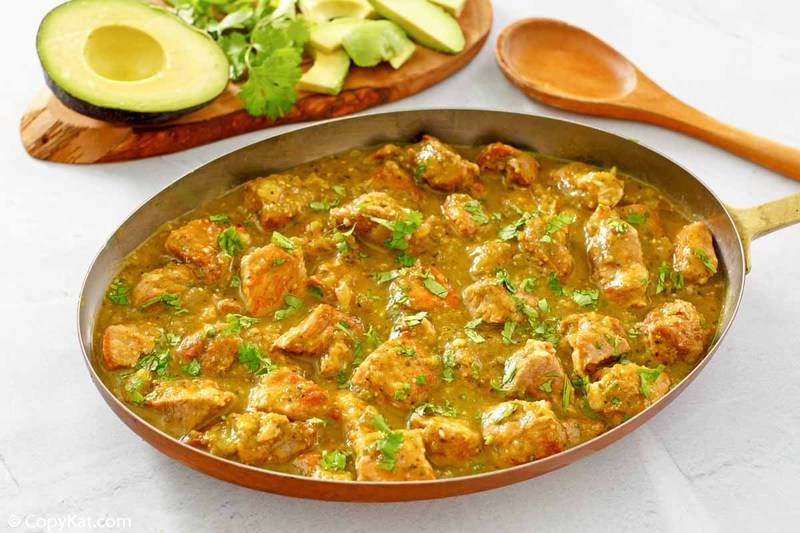 chili verde in a skillet, a wood spoon, and fresh avocado