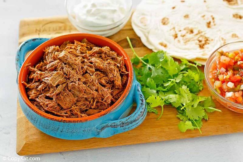 a bowl of shredded beef barbacoa, cilantro, sour cream, salsa, and tortillas