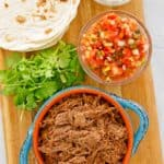 overhead view of beef barbacoa, cilantro, salsa, tortillas, and sour cream