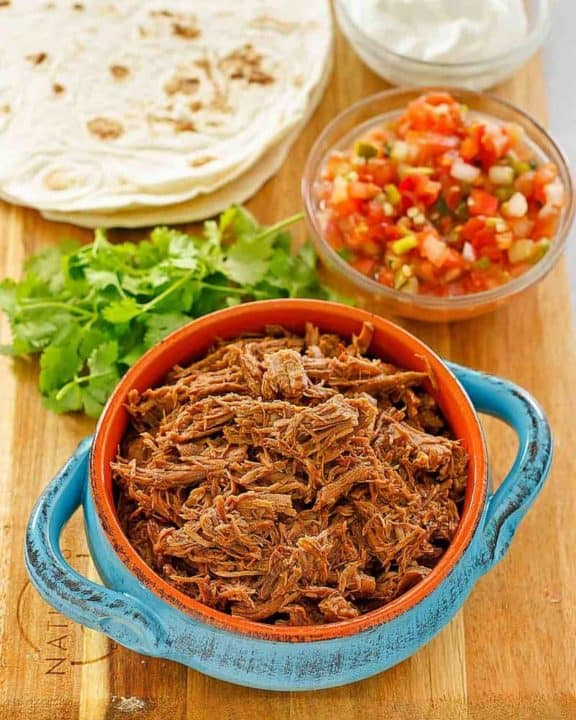 beef barbacoa, cilantro, salsa, tortillas, and sour cream