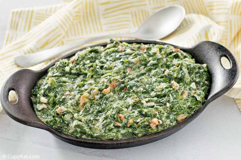 homemade Lawry's creamed spinach with bacon in a dish, a spoon, and cloth napkin