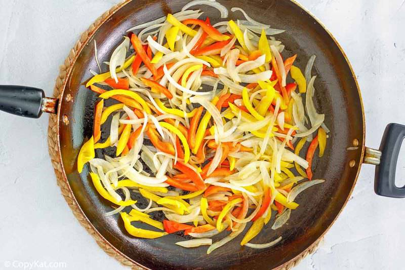 sliced bell peppers and onions in a skillet