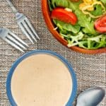 overhead view of a bowl of Russian dressing and a salad