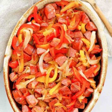 overhead view of smoked sausage and peppers in a serving dish