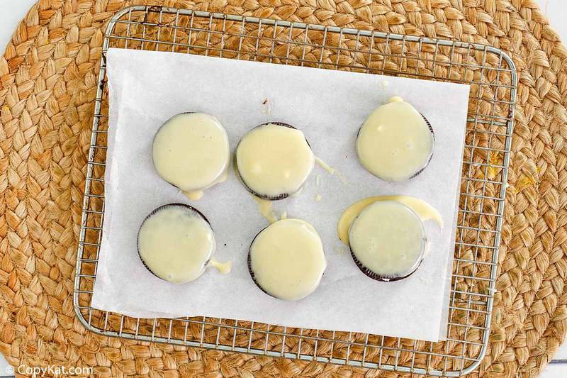 Oreos covered in white chocolate on a baking rack