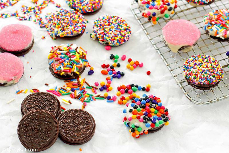 Oreo cookies topped with white chocolate and candy sprinkles