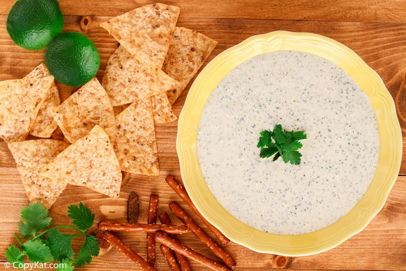 a bowl of homemade Chuy's creamy jalapeno dip, tortilla chips, and limes