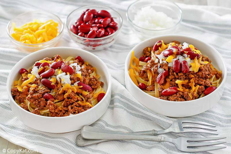 two bowls of Cincinnati chili and small bowls of cheese, kidney beans, and chopped onions