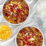 overhead view of bowls of Cincinnati chili, shredded cheese, chopped onions, and kidney beans