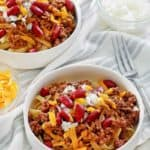 bowls of Cincinnati chili topped with cheese, onions, and kidney beans