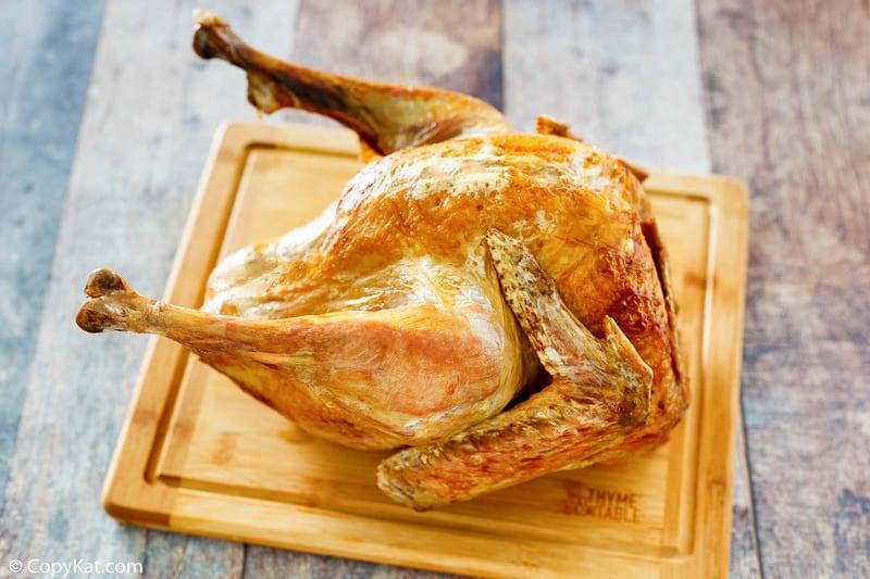 a whole deep fried turkey on a cutting board