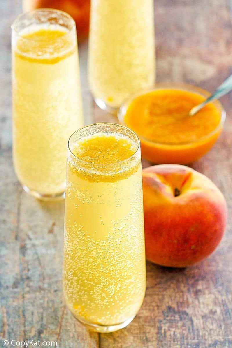 homemade Harry's Bar Bellini cocktails, a fresh peach, and peach puree